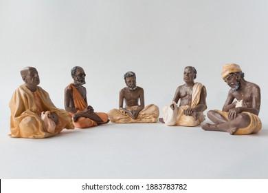 Isolated figurines of yogi teachers in a row. Art, figures, real, sky, pray, concentration, faith, belief, hinduism, teachers, religious, concentration, meditation, calm, peach, concept, India, orange