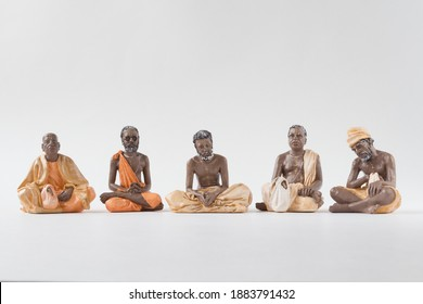 Isolated figurines of yogi teachers in a row on white background. Art, figures, real, sky, pray, concentration, faith, belief, hinduism, teachers, religious, concentration, meditation, calm, peach, co