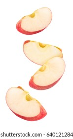 Isolated flying apple wedges. Four falling pieces of red apple fruit isolated on white background with clipping path