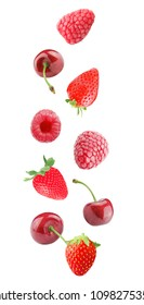 Isolated flying mixed red berries. Falling cherry, strawberry and raspberry fruits isolated on white background with clipping path as package design element and advertising.