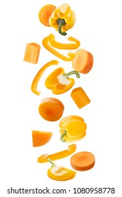 Isolated flying vegetables. Falling fresh yellow sweet pepper and carrots isolated on white background with clipping path as package design element and advertising.