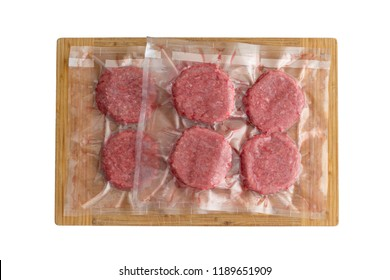 Isolated fresh beef burger patties in a vacuum pack ready to be frozen for sous-vide cuisine viewed from above on wood
