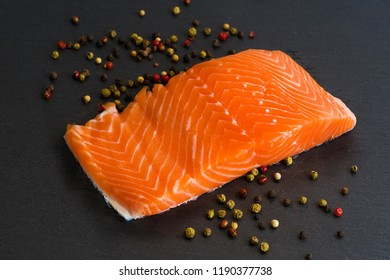 Isolated fresh raw salmon filet on black background with pepper