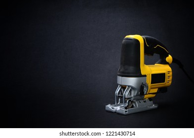 Isolated front side yellow electric jig saw on a dark background
