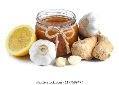 Isolated. Garlic, a honey jar, ginger and lemon on a white background. Maintenance of immunity. Treatment of colds and flu. Products for immunity. Immunity concept.