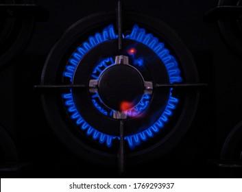 Einziger Gasbrenner mit Metallteilen auf einer schwarzen Glasküche, die einen Kreis von blauen Flammen bildet