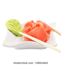 Isolated ginger and wasabi on white background with chopsticks