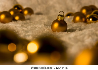Isolated gold Christmas decoration ball on white background and blurry other balls.