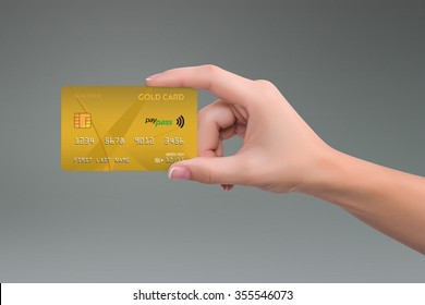 Isolated gold credit card in woman hand on gray background