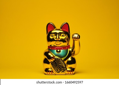 Isolated golden Maneki Neko Japan lucky cat on the yellow background. The concept of time and expectation of good luck.