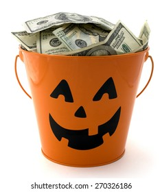 Isolated halloween bucket filled with cash.