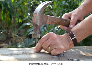 Isolated hand hitting nail into wood with a hammer