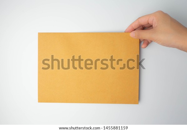 Isolated hand holding brown letters (document, file, notation, monograph or paper)