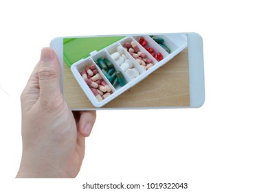 Isolated Hand holding smartphone horizontal to take a photo of pharmacy capsule pill and another drug for reminding with white background