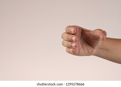 Isolated hand holding something like a glass, can or phone.