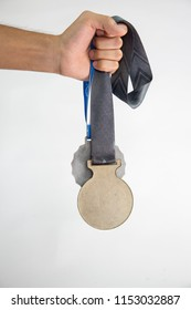 Isolated hand of a person holding medals from a race or competition. White backgorund. First and second place
