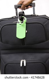 Isolated hand picks up luggage with bright green tag