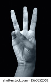 Isolated hands of male teenager doing Varuna Yoga Mudra on black background.Male doing Varuna Yoga mudra to clear congestion to help with sinus and throat problems isolated on black background.