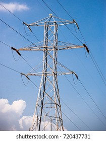Isolated high tension tower and power lines against blue sky with white puffy clouds.
