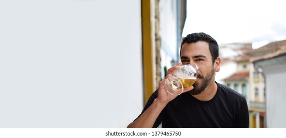 Isolated Hispanic latin arab indian bearded handsome guy drinking beer with a a blurred colonial city background, and plenty of horizontal copy space. Ads, banner, blank space and advertising concept