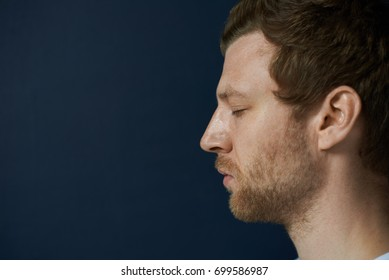 Isolated horizontal profile portrait of bearded young guy closing eyes while meditating, relaxing body and mind, standing at blank studio wall, having calm and peaceful expression on his face