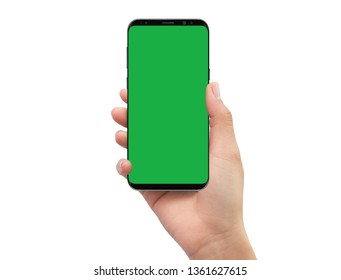 Isolated human right hand holding black mobile smart phone with green screen for video production