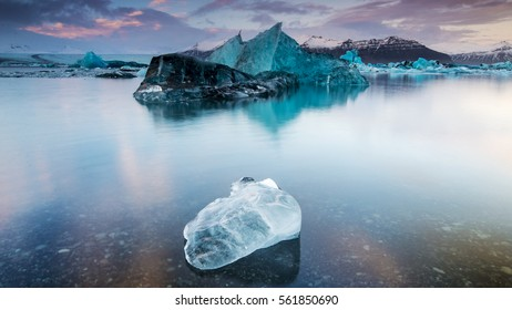 Isolated iceberg in the middle of the lake, with blue glacier