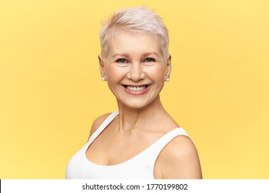 Isolated image of attractive mature retired woman with stylish pixie haircut being in good mood smiling broadly at camera wearing earrings and white tank top. Beauty, femininity and aging concept