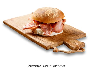 Isolated image of a bacon roll on a wooden board, with tomato sause.