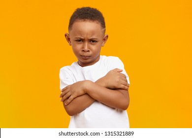 Isolated image of funny cool African American little boy frowning and keeping arms crossed on his chest against blank yellow studio wall with copy space for your text. Life perception and attituve