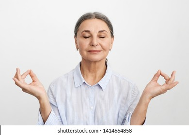 Isolated image of happy middle aged businesswoman raising positive vibrations, keeping eyes closed while meditating for wellbeing, using visualization. Zen, meditation, relaxation and age concept