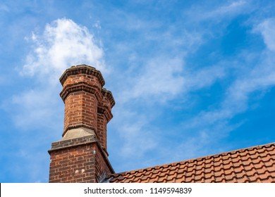 Isolated image of a pair of very old brick-built chimneys showing there unique, hexagonal design against a summer sky. The chimneys are still in use during the cold months.