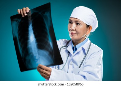 Isolated image of a radiologist examining an x-ray over a blue background