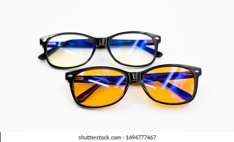 Isolated image of two blue light blocking glasses (day and evening, yellow/orange lenses) on a white background - health, good sleeping and wellness concept for melatonin and circadian rhythm