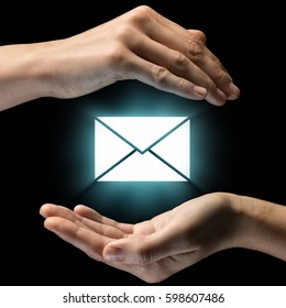 Isolated image of two hands on black background. Envelope icon in the center, as a symbol of confidentiality of correspondence. Concept of confidentiality of correspondence.