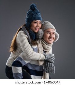 Isolated image of a young couple in winter wearing piggybacking over a grey background