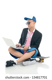 Isolated image of a young man dressed funky sitting on a skateboard and using laptop