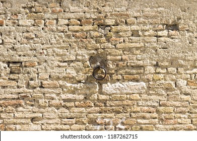Isolated iron handle in a medieval wall background (Marche, Italy, Europe)