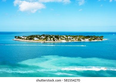 Isolated island off the coast of Key West surrounded by blue ocean waters and sport boats