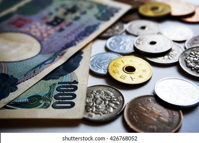 Isolated Japanese currency (yen) with its Asian symbols in the form of coins and bank notes on the white background