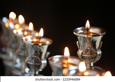 Isolated Jewish menorah (candelabra) used traditionally on the holiday of Hanukkah, fully lit, on a black background