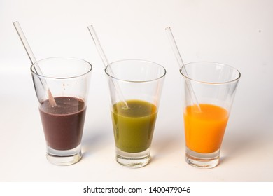 isolated juice cups in white background- açaí fruit, green and orange juices-with washable glass straws to drink them. Concept of recycling and reducing the amount of litter in the planet and oceans.