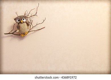 Isolated knitted owl on a branch on a beige background