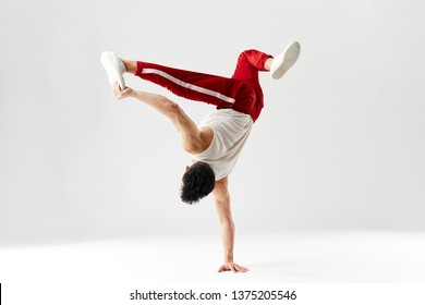 Isolated Korean hip hop male break dancer dancing on white background, performing air split stout element of downrock breakdance