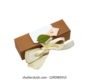 Isolated kraft paper packing box, decorated with blank frame, beige satin ribbon and Calla flower. Wedding or Birthday present