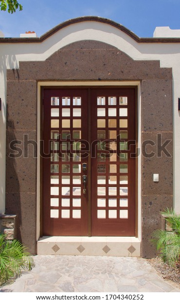 An isolated large, ornate brown wooden door on an adobe-style condominium.