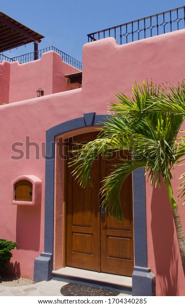 An isolated large, ornate brown wooden door on a pink, adobe-style condominium.