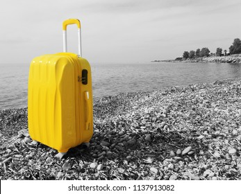 Isolated Large Yellow Polycarbonate Suitcase on the beach on gray background