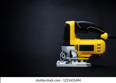 Isolated left side yellow electric jig saw on a dark background