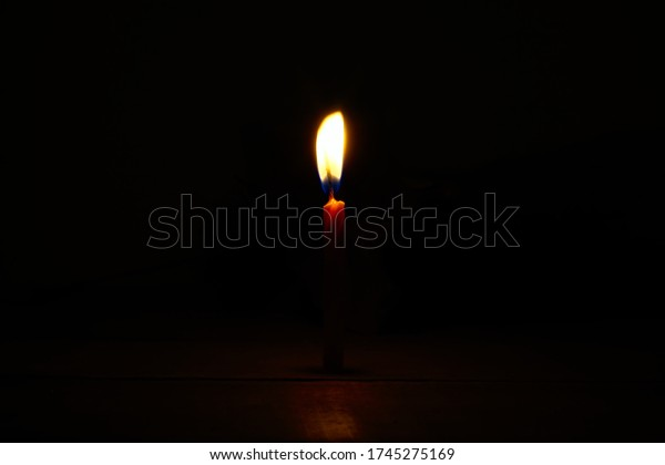 isolated-lighted-candle-dark-background-